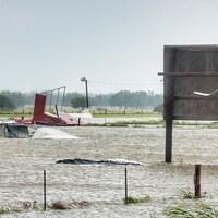 Des débris, vraisemblablement des ruines d'habitations, sont transportés dans les champs par l'eau et le vent, devant un panneau de signalisation.
