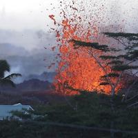 De la lave surgit d'une fissure du volcan Kilauea près d'une habitation à Hawaï.