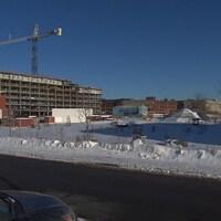 Un terrain vague et enneigé non loin d'un édifice à étages en construction.