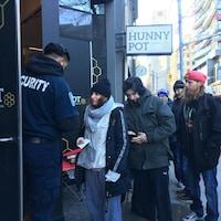 Photo de personnes en file sur le trottoir qui montrent leur carte d'identité à un agent de sécurité.
