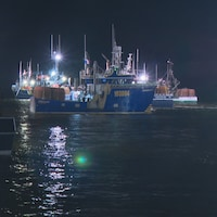Plusieurs bateaux s'éloignent du quai en pleine nuit.