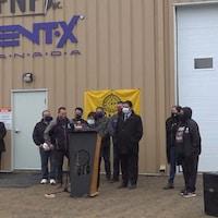 Des personnes sont derrière un podium devant une usine.