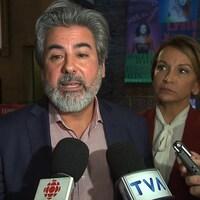 M. Rodriguez s'exprime devant des journalistes. Deux femmes se tiennent à côté de lui.