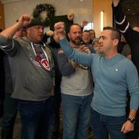 Des travailleurs lèvent le poing en scandant des slogans.