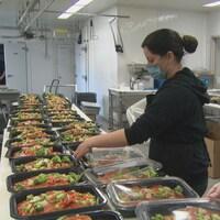 Des élèves emballent des plats dans une cuisine.