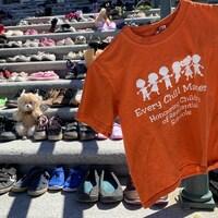 Les marches du Palais législatif de Regina, en Saskatchewan, avec un chandail orange et 215 paires de souliers en l'honneur des restes d'enfants retrouvés près du pensionnat pour Autochtones de Kamloops.