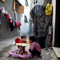Une jeune fille joue avec son frère dans un camp de réfugiés, dans la bande de Gaza.