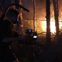 Un homme vu de côté qui filme un incendie de forêt.