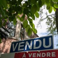 Une pancarte immobilière sur laquelle on peut lire Vendu.