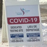 Une petite pancarte posé sur la neige sur laquelle il est écrit COVID-19, sur fond rouge.