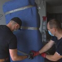 Des déménageurs recouvrent un meuble d'une enveloppe protectrice.