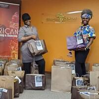 Pulchérie M'Boussi et Jacky A. Yenga entourées de sacs de denrées.