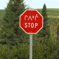 Panneau d'arrêt bilingue en anglais et en langue crie.