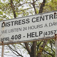 Sur le panneau, il est écrit : centre de détresse, nous écoutons 24 h sur 24. Est ensuite écrit le numéro de téléphone où appeler à l'aide.