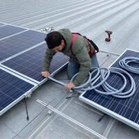 Un homme travaille sur la mise en œuvre d'un panneau solaire.