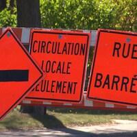 Panneaux sur lesquels est écrit : « Circulation locale seulement » et « Rue barrée »