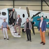 Cinq hommes se tiennent debout tout près d'un petit avion.