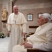 Le pape François sourit face au pape émérite Benoît XVI et aux cardinaux. Personne ne porte de masque.