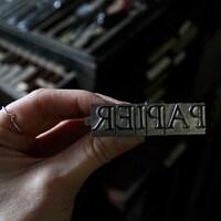 Une main tient une série de caractères typographiques en métal destinés à imprimer le mot «papier».