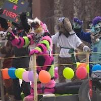 Des membres de la parade de la Fierté gaie sont costumés et saluent sur un char de la parade.