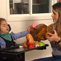 Eugénie Côté-Robitaille joue avec sa fille, Élisabeth Laplante, atteinte de la paralysie cérébrale.