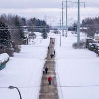 Des gens marchent sur une piste linéaire en hiver.