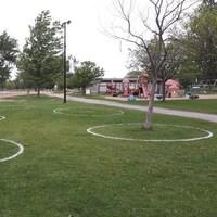 Des cercles de distanciation peints sur le gazon du parc Mooney's Bay