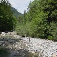 Deux personnes sont au bord d'une rivière peu profonde, entouré de rochers et bordés de grands conifères.