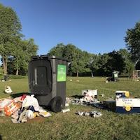 Une poubelle entourée de cartons de bières
