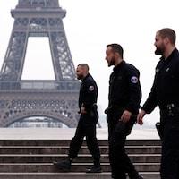 Trois policiers près de la tour Eiffel.