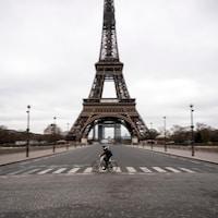 Un homme à vélo traverse une rue déserte sous la tour Eiffel.