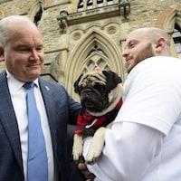 Erin O'Toole, un chien et un homme sont debout devant le parlement.