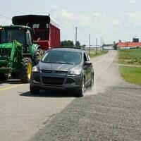 Une voiture dépasse un véhicule agricole sur une route de campagne.