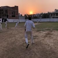 Un homme de dos s'avance sur le terrain tandis qu'un autre joueur lance la balle.