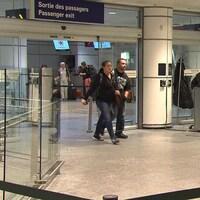 Des gens sortent par la sortie des passagers à l'aéroport Montréal-Trudeau.