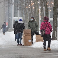 Des gens marchent dans la rue alors qu'il neige.