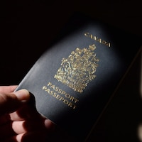 Une main tend une passeport canadien.