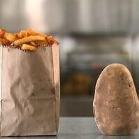 Sac de papier rempli de frites, placé à côté d'une pomme de terre encore terreuse.