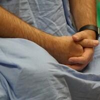 Un patient attend les mains croisées en jaquette bleue.