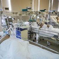 Plusieurs patients sont alignés dans une unité de soins intensifs.