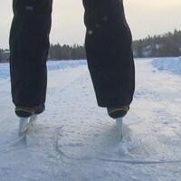 Un homme, photographié de dos, patine sur le lac Kénogami.