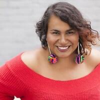 Patricia Cano porte un pull-over rouge, des boucles d'oreilles multicolores, elle a les cheveux ondulés bruns