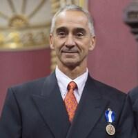 Il sourit et porte l'insigne de l'Ordre national du Québec sur son veston.