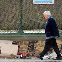 Un homme passe à côté d'une personne qui dort dans un carton et dont on ne voit dépasser que les pieds.