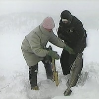 Deux pêcheuses tire une grosse morue des glaces de la rivière Saguenay.