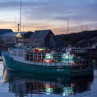 Un bateau plein de casiers à homards, à l'aube près du rivage.