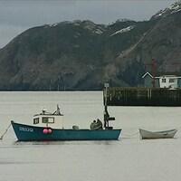 Un petit bateau de pêche sur les eaux, proche de la côte.