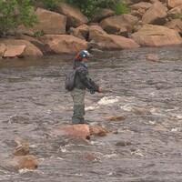 Une femme pêche dans la rivière.