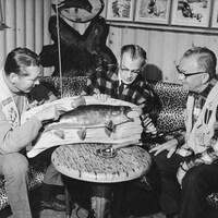 Dans une pièce remplie d'objets associés à la chasse et la pêche dont un poisson naturalisé, l'animateur Serge Deyglun, le réalisateur Marc Perron et l'animateur Richmond Pelletier, discutent autour d'une table.