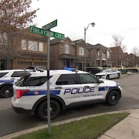 Trois véhicules de police bloquent la rue où l'enfant mort a été trouvé.